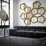 gold-frame ornamental mirrors in pentagon shape unique spot lighting comfy black sofa