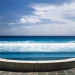 gorgeous infinity pool stone tiled flooring grey concrete pool border half round ceramic spa border beautiful beach scenery