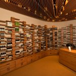 gorgoeus store design with clustered wall shelves also ravishing wavy ceiling with elegant brown wooden cashier area in concrete flooring