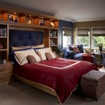 grey carpet flooring white ceiling brown and navy wall wood side table blue armchairs wood table blue headboard red bed cover wooven blinds cream and blue pillows