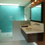 grey tiled flooring floating wood vanity with white counter square undermount white sink black square mirror frame blue tiled shower wall downlight brown and white wall unique wall mounted lighting