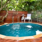 high-class round plunge pool single wood relaxing chair round wood table with unique feet design  steel pool fences wood box for equipment pool enclosure hardwood floors idea