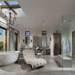 interesting gray bathroom design with elegant bathtub and cozy fabric seating with transaprent glass shower in granite tile flooring