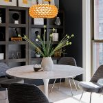 interesting small dining room with elegant dark gray chairs also ravishing round wooden table with frech potted plant and giant wall mount shelve in laminate flooring