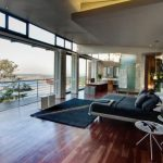 interestng black bedroom with low profile bed design overlooking city view with eclectic kitchen area in laminate flooring