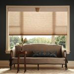 large brown window shade twin artistic wall-lamp  comfy single sofa in brown tone small round wood table with fresh flower ornament good-look brown carpet
