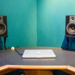large monitor desk with two audio systems stands a notebook set