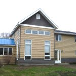 large pole barn house with bricks wall two additional bar house buildings with many windows