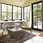 Large Under Window Book Shelves  Sliding Glass Door With Black Wood Frames  Red Entryway Rug  Shabby Look Wood Table A Pair Of Reading Chairs In Cream Color Persian Rug