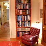 leather-coat reading chair corner standing lamp in gold-accent book shelves