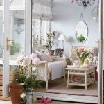 light gray painted wall rattan armchairs rattan coffee table hanging mirror colorful flower bouquet pink rug white lamp floral patterned cushions how to make spring smell home