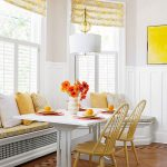 long bay window bench with cozy mattress and colorful pillows casual white pendant lamp white table and a pair of rattan chairs pretty flower arrangement a pretty porcelain vase  bay windows and their shading