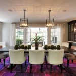luxurious dining room concept with elegant white leather chairs and long wooden table feat twin chandelier and white framed window in multiple accent of purple in rug