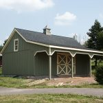 mini green pole barn home building with wood siding artistic chimney single framed window