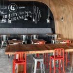 modern cafe concept with ravishing black wall detail also unique wavy wooden ceiling feat large wooden table and cozy chairs in concrete flooring