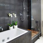 modern narrow tub idea with black natural stone frame twin vivid floral ornaments frameless glass door shower zone with stainless steel shower unit minimalist black wall decoration