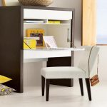 modern studying desk with folding top deks and shelves  white-cotton chair with black wood legs some books gadget device