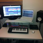 monitor desk with white platform a computer unit a notebook set a unit of mini keyboard instrument twin audio system