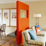 movable room divider in bright orange a pair of beautiful strips-patterns chairs a standing lamp with metal stand extra-big photo frames hardwood floors