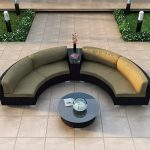 outdoor long curved banquette seat unit with table-divider round glassy table twin clay-made pot with ornamental plants