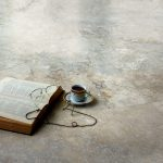 porcelain tiles with marbles' natural grout lines an old book a cup of coffee reading-glasses