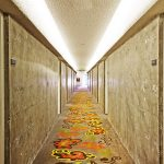 raw concrete wall creame hotel room door bright colored patterned carpet floor white ceiling raw interior design of hotel hallway The Line Hotel in Koreatown Los Angeles