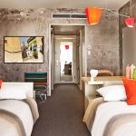 raw concrete wall gray carpet floor wooden headboard as well as table colorful chair simple red pendant lamp double bed room amazing painting raw interior design of The Line Hotel in Koreatown Los Angeles
