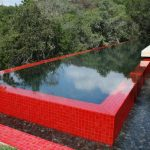 red tiled swimming pool red tiled pool border beautiful green scenery white patio flooring black deck chair red curtain grass outdoor ground