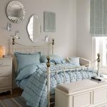 round sheffield decorative mirror in glass frame ornamental mirror with stainless steel frame classic bed unit comfortable bed with blue bedcover freestanding cabinets glass vase with vivid rose flowers full-cylinder table lamp