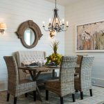 setee seating in light grey color aesthetical rattan-made dining chairs meaningful abstract painting in white frame classic pendant lamp twin small wall-lamps a unique-shape ornamental mirror attractive rug