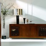 sideboard in rustic style with glass-door shelves glowy-sliver-cap table lamp with black metal stand two ornamental wine glass attractive vivid plant ornament