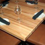 simple light brown wood desk top  sets of wine glasses  sets of plates