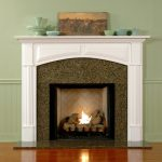 simple minimalist firebox with white wood mantel colorful ceramic ornaments frameles painting wood-finish flooring