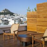 simple rustic rooftop wooden wustic coffee table wooden vintage armchairs wooden enclosure wooden rooftop floor beautiful Athens landscape the unique hotel design of the NEW hotel in Greece
