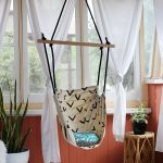 simple white curtain cloth-made hanging chair with simple pattern vivid floral ornaments rattan table mini white furry carpet unique style of flooring