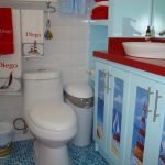small blue tile flooring white toilet white tiled wall blue cabinet with gorgeous hand painted beach scene red counter white bowl sink white and red towels