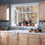 small garden window in the simple kitchen flower ornament and decorative clay-made pots twin top cabinets units wood finish cabinetry sink and faucet units cooking tools
