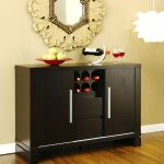 smaller black wood  kitchen sideboard  with unique storage design  red plate for fruits  a metal wine bottle stand a pair of wine glasses luxurious decorative mirror hardwood floor sparkling white pendant lamp