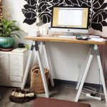 standing desk with wood top desk flat screen computer set small cabinetry fresh plant ornament floral art wall decoration shelving unit in red color bag made from rattan