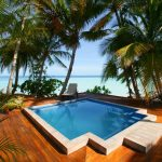 tropical pool landscape design a unique-shape pool hardwood floors  beautiful  free ocean background minimalist relaxing chairs for outdoor pool area