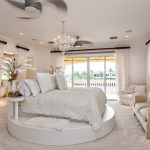 white bedroom cocnept with elegant princess bed style also cozy cream sofa with luxurious chandelier and large glass window also wide white curtain in large white carpet