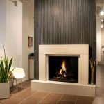white fireplace mantel with vertical planks wall system  a white plastic  chair with tiny metal legs ceramic subway tiles floor