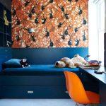 white floor orange chair blue desk blue shelf cabinet white ceiling blue bed frame with drawers blue bedding set white framed winodow orange with black monkey themed wallpaper