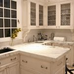 white granite countertops white kicthen cabinet white cupboard white framed window white wall undermount black sink white sconces white tile flooring cream and black diagonal tile flooring grey mat