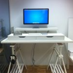 white minimalist standing desk with unique feet  computer set headphone