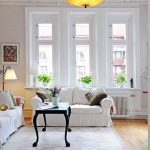 white painted wall wooden floor light gray rug black painted coffee tabe white sofa white painted window frame beautiful flower bouquet small white vas how to make spring smell home