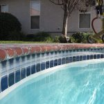 white swimming pool cover dark blue decorative tile on the swimming pool edge grey wall white blinds white framed windows red brick pool border gold pool cleaner machine