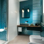 white tiled wall white shower flooring blue tiled wall mosaic blue shower wall glass shower door floating wood vanity grey square sink square simple mirror white sconces white framed window white toilet