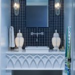 white wall white vanity green and blue towels wooven basket unique wall white sconce rectangular mirror white towel white table lamp white sink dark blue tiled wall