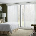 white window semi-transparent shutters comfortable bed a pair  cozy chairs higher round glass table with beautiful fresh flowers soft carpet white-tone standing lamp